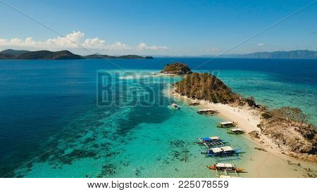 Aerial view of tropical beach on the Bulog Dos Island, Philippines. Beautiful tropical island with sand beach, palm trees. Tropical landscape: beach with palm trees. Seascape: Ocean, sky, sea. Travel concept.