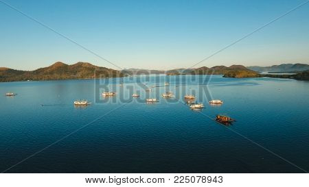 Seascape tropical bay with boats, surrounded by mountains on the island. Aerial view: Beautiful tropical sea bay. Scenic landscape with mountain islands and blue lagoon. Coron, Philippines, Palawan, Busuanga. Travel concept,