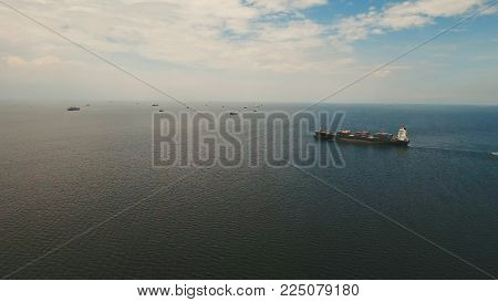 Aerial view Cargo ships in the Bay of Manila. Large container ship in the sea. Flying over the water surface of the sea with ships, blue sky and clouds. Philippines, Manila.
