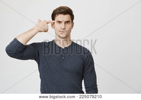 Horizontal portrait of Caucasian male with stubble and trendy haircut pouting lips in casual clothes bored with work, shooting himself with finger gun gesture. Human face expressions and emotions