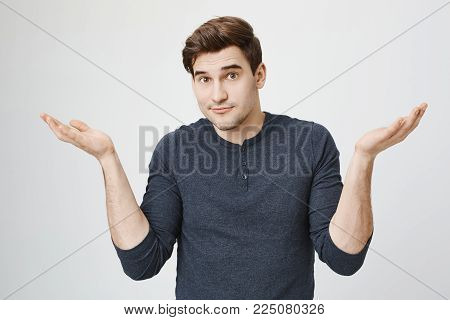 Indoor portrait of confused handsome guy showing I have no idea gesture, shrugging shoulders and raising hands, standing against gray background. Sorry I did not know it was your food in fridge.