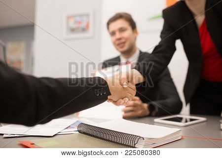 Close up of two business people shaking hands against blurred background of meeting in modern office, copy space