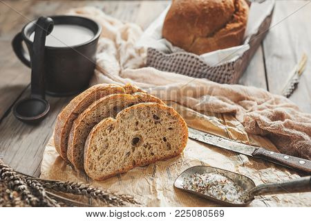A beautiful loaf of sourdough bread from white wheat on a plate on a linen edge. Homemade pastries. The horizontal frame.