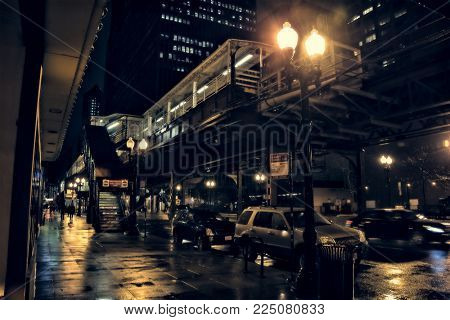 Chicago city street scene in the Loop with elevated CTA L train platform, stairs, pedestrians and cars at night during rain.
