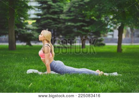 Fitness, woman training yoga in cobra pose outdoors in the park, copy space. Young slim girl makes exercise. Stretching, wellness, calmness, relax, healthy, active lifestyle concept
