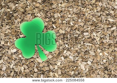 Shamrock clover made of paper on a background of wooden sawdust. St.Patrick 's Day.