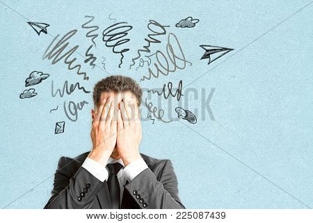 Businessman Covering Face On Abstract Background With Scribble. Risk And Confusion Concept