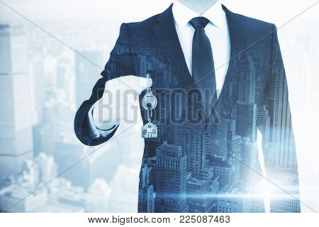 Businessman Holding Key With House Keychain On Abstract City Background. Real Estate And Housing Con