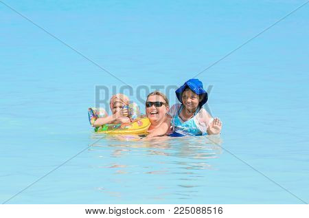 Varadero beach, Cuba, Apr. 23, 2015, gorgeous amazing view of happy joyful woman with her children enjoying theire vacation time, swimming in the ocean on sunny beautiful day at Cuban Varadero beach