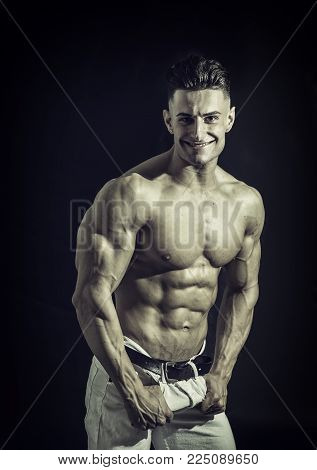 Good Looking Young Gym Fit Man Showing His Sexy Six Pack Abs While Looking at the Camera. Isolated on Black Background.