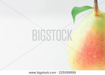 Single Ripe Organic Pear In Pastel Green Yellow Red Colors With Stem Leaf On White Table. Elegant Mi