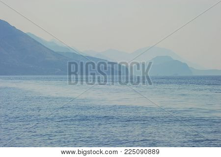 A view of a sea and mountains in haze. Smokey mountains look mystique. The closest ones are the darkest and far are very light.