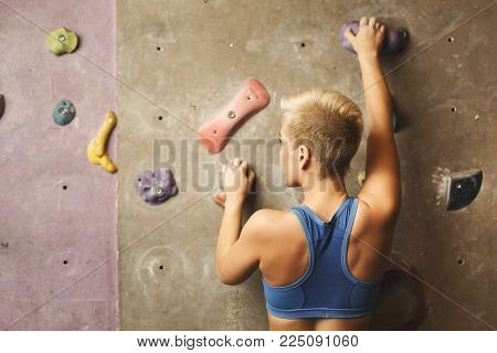 Young happy woman practicing rock-climbing on artificial wall indoors. Active lifestyle and bouldering climbing, reaching the top concept