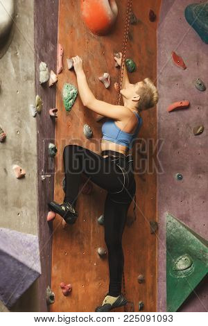 Female fitness professional sport climber having training at bouldering gym. Young happy woman smiling while climbing artificial rock wall, reaching the top concept