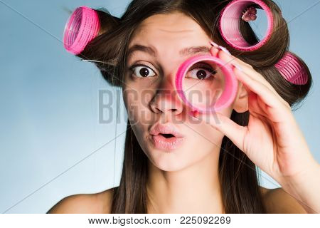 woman with big curlers on her head on a blue background