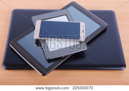Stack Made Of Different Gadgets: From Smartphone, Ebook Reader, Tablet Device And A Notebook On A Wo