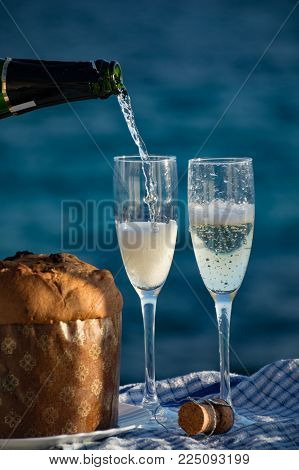 Sweet Fruit Chrismas And Easter Cake Panettone With Two Glasses With Champagne Served Outside With B