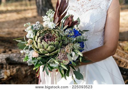 Wedding beautiful bouquet of protea in the hands of the bride. Closeup.