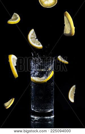 Lemon slice splases in glass o water Freeze time concept, Lemon in a glass, freezing time, falling lemons, low key