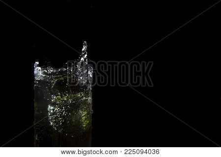 Green broccoli falling in water on white with air bubbles, Broccoli in water, freezing time, splashing water