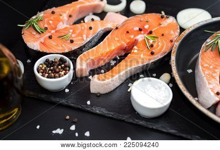 Fresh raw unprepared fish salmon or trout, steaks, in a skillet for cooking, with salt, pepper On black stone concrete table, copy space top close view
