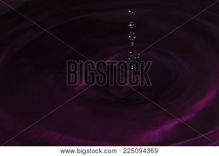 Beautiful splash of water drop. Freeze action. High-speed shooting of water drop. Beautiful drops of stop time, water splashing close up. Crystal clear water waves, drops and sprays.
