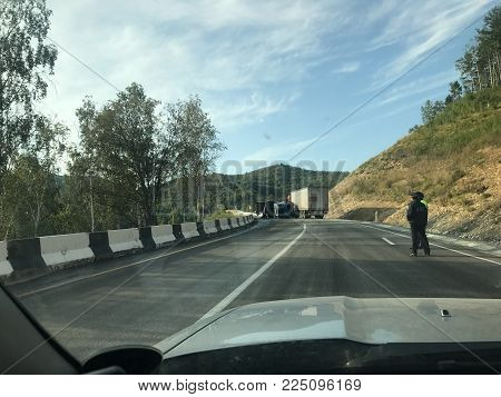 The accident with two trucks. The distance the accident with two trucks on the road. The route goes through the forest. Not far from the accident are the police. Russia, Irkutsk - 28 Aug 2017