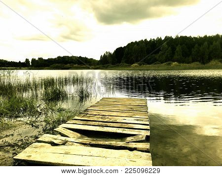 Old pier near the lake. Bleak landscape - the old pier with broken planks leads to the lake. In the background lies a forest.