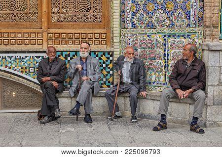 Tehran, Iran - April 27, 2017:Iranian elderly pilgrims are sitting near the Shrine of Hazrat Abdulazim al-Hasani.