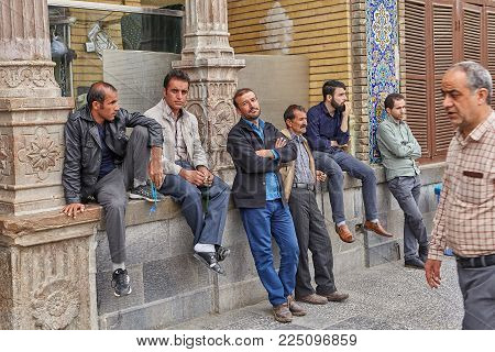 Tehran, Iran - April 27, 2017: Iranian men sit near a column in the Shrine of Hazrat Abdulazim al-Hasani.