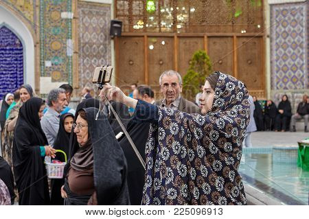 Tehran, Iran - April 27, 2017: Iranian woman in hijab takes pictures of herself on a smartphone in the background of the Shrine of Hazrat Abdulazim al-Hasani.