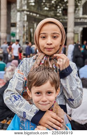 Tehran, Iran - April 27, 2017: Iranian boy and girl in religious veil stand and hug near the Shrine of Hazrat Abdulazim al-Hasani.