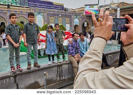 Tehran, Iran - April 27, 2017: Iranian man takes pictures of children on a smartphone near the Shrine of Hazrat Abdulazim al-Hasani.