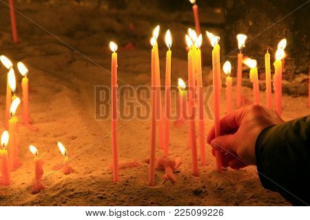 a human hand puts a candle on the health in the church. religious sacrament