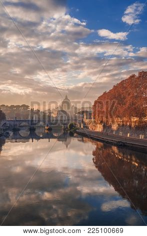 Autumn sunset over River Tiber with Saint Peter Dome in the evening haze
