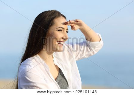 Happy woman scouting with hand on forehead on the beach in a sunny day