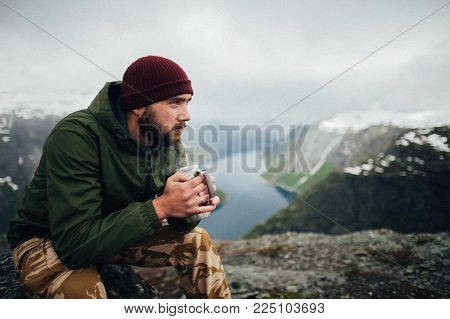 Man traveler meet the dawn sitting on Trolltunga rocky cliff edge in Norway mountains Travel Lifestyle adventure extreme vacations outdoor alone above clouds