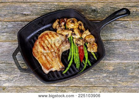 A thick juicy broiled steak topped with Grilled steak with asparagus mushroom