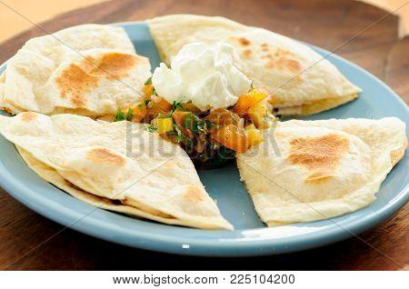 chicken quesadilla with salsa and sour cream