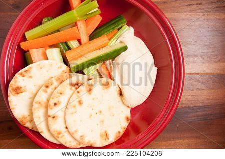 home made hummus or hummous with naan bread and vegetable sticks