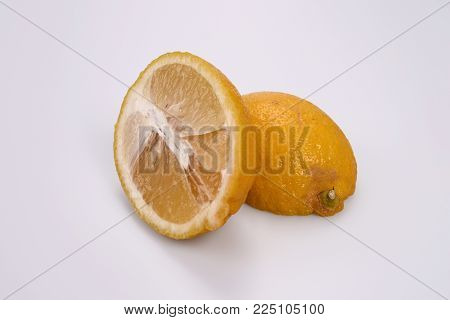 Two halves of cut lemon on white background: on the left half with fresh pulp, on the right with yellow peel.