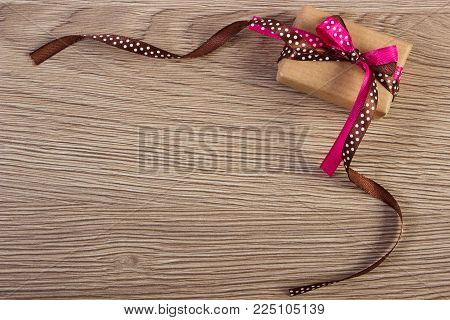 Wrapped gift with ribbon, decoration for Valentines Day, copy space for text on rustic board