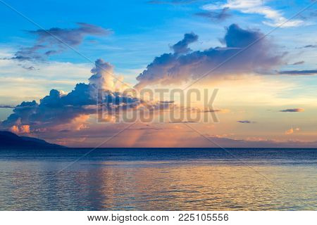 Sunset sky and sea. Seaside sunset with orange and blue clouds. Tropical sea and distant island silhouette. Idyllic seaview. Romantic landscape of still sea. Tropical sunset seascape. Travel photo