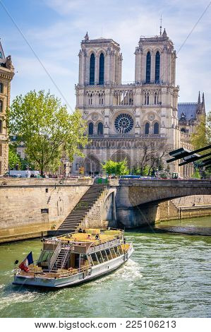 Notre-dame-de-paris Cathedral And A Boat Passing By On The Seine In Paris