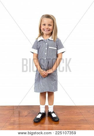 young beautiful and happy child girl 6 to 8 years old blond hair and blue eyes smiling excited wearing school uniform isolated on white background in kid education concept