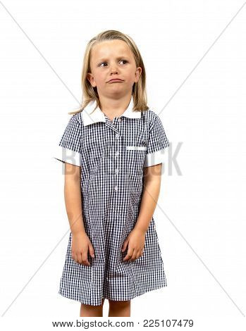 young beautiful and moody schoolgirl in uniform looking tired bored and upset in frustrated face expression isolated on white background in education and back to school concept