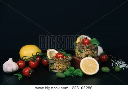 Dietary menu healthy vegan salad of vegetables broccoli mushrooms spinach and quinoa in a jar on a black background.