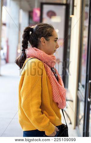 Young Woman With Braided Pony Tail And Yellow Sweater With Zipper In The Back Stands In The Street