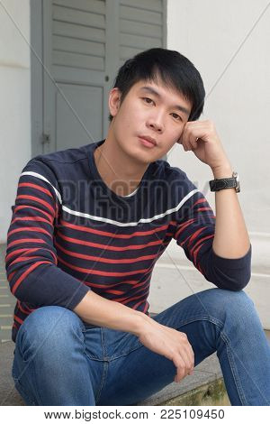 A young asian chinese male staring blankly at the camera with hand resting on his head