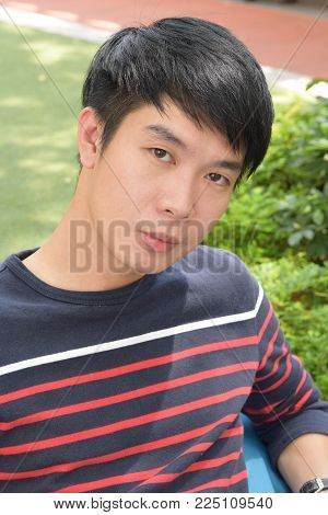 A young asian chinese male looking at camera outdoor